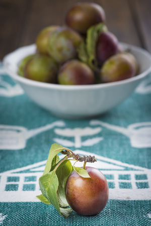 Closeup from ecological plums with a fruit bowl behind photo