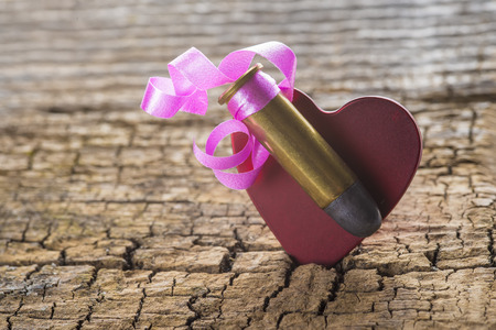 38 caliber: Bullet with a heart decorated like a gift on a wooden background
