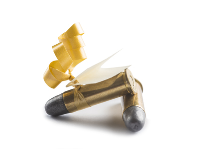 Bullets with a greeting card decorated like a gift and meaning threat isolated on a white background photo