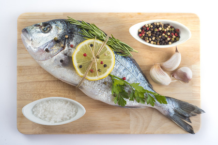 sparus: Raw gilt-head sea bream with spices and herbs on a cutting board ready to be cooked