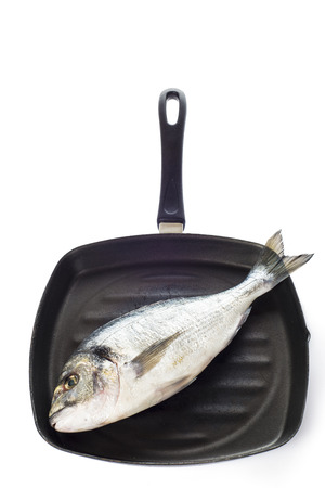 sparus: Raw gilt-head sea bream fish on a pan isolated on a white background