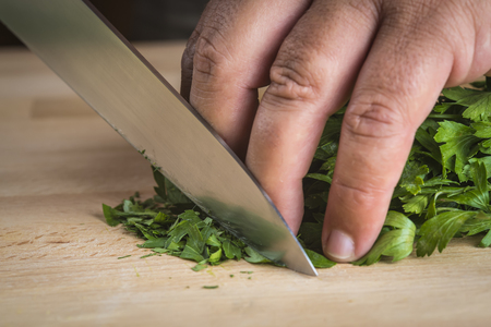 Chef chopping parsley leaves with a knife on a cutting board