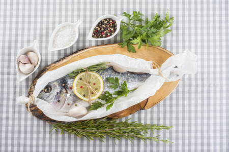 sparus: Raw gilt-head sea bream with herbs and spices in a bakery release paper prepared to be cooked