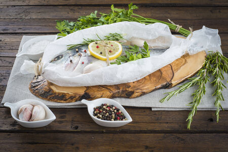 Raw gilt-head sea bream with herbs and spices in a bakery release paper prepared to be cooked photo