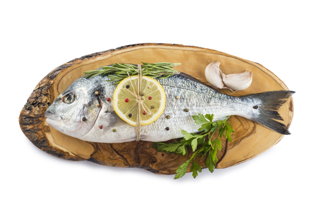 sparus: Raw gilt-head sea bream with spices and herbs on a cutting board Stock Photo