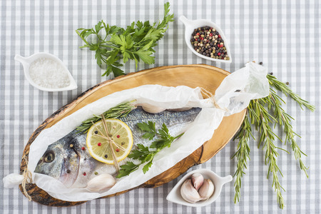 sparus: Raw gilt-head sea bream with herbs and spices in a bakery release paper