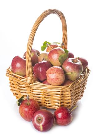 canastas con frutas: Una canasta con manzanas rojas frescas aisladas sobre un fondo blanco Foto de archivo