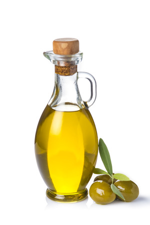 Extra olive oil bottle and green olives with leaves isolated on a white background Stockfoto