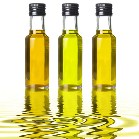 Three glass bottles of different extra olive oil on liquid reflections photo