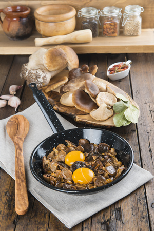 edulis: Cooking scrambled eggs with mushrooms and natural ingredients and spices Stock Photo