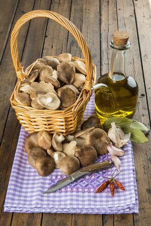 aceite de cocina: Cesta con las setas, aceite de oliva y los ingredientes para cocinar en la mesa de la cocina