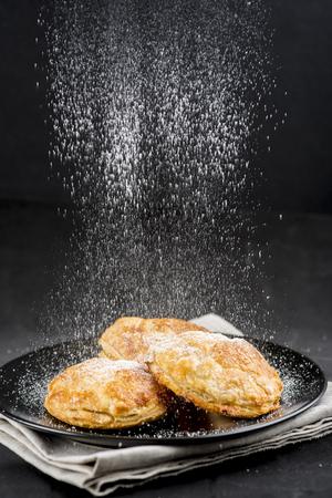 Spolverata di zucchero a velo su torte su sfondo nero