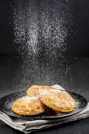 Sprinkling powdered sugar on cakes on a black background