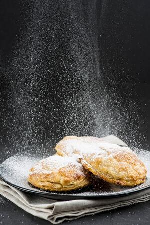 powdered sugar: Sprinkling powdered sugar on cakes on a black background
