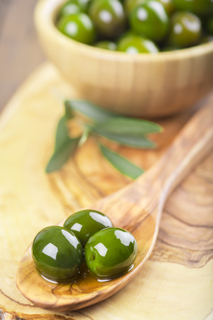 Wooden spoon and bowl with green olives on a cutting board on the table of the kitchen photo