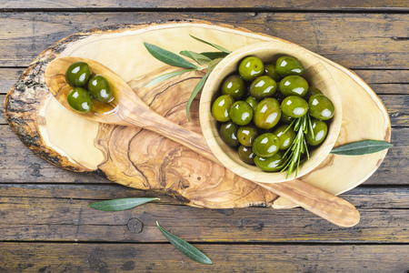 Wooden spoon and bowl with green olives on a cutting board on the table of the kitchen Standard-Bild