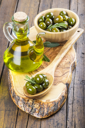 Wooden spoon and bowl with green olives and a jar with olive oil on a cutting board on the table of the kitchen photo