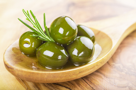 wooden spoon with green olives, olive oil  and some fresh rosemary on a cutting board