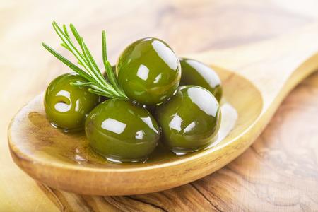 houten lepel met groene olijven, olijfolie en verse rozemarijn op een snijplank