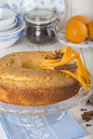 cake stand: Homemade orange sponge cake on a glass cake stand over the kitchen table