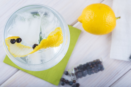 mixed fruit: Gin and tonic on a highball glass with a lemon twist and juniper berries