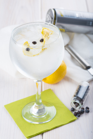 highball: Gin and tonic on a highball glass with a lemon twist and juniper berries