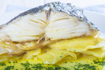 cod oil: Salted cod fish oven baked with potatoes onion and olive oil Stock Photo