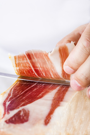 Professional cutter carving  slices from a whole bone-in serrano ham