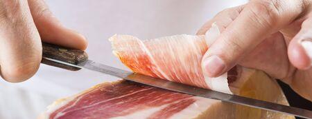 serrano: Professional cutter carving  slices from a whole bone-in serrano ham