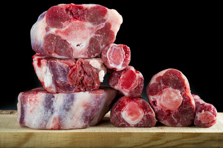 Fresh and raw oxtail cut on the cutting board isolated on a black background Standard-Bild