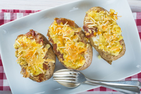 Twice baked potatoes stuffed with meat, jam, cheese and egg Standard-Bild