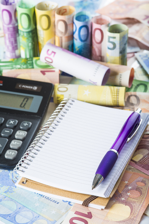 money background: Calculator pen money and notebook on a banknotes background