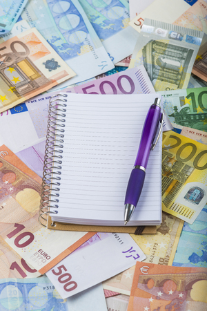 money background: Notebook and pen on a money background made of banknotes