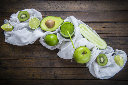 verduras verdes: Fruits and vegetables with a glass of fresh green smoothie on a wooden table Foto de archivo