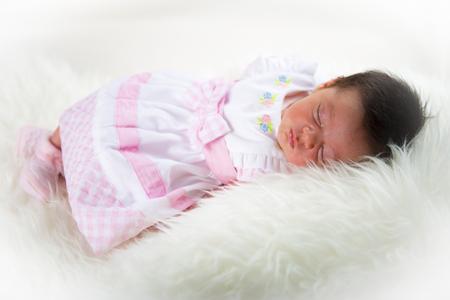 girl lying studio: Newborn girl lying happy and relaxed on a blanket of white hair and dressed in pink