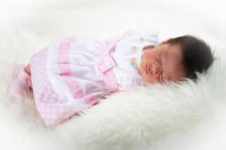 jolie pieds: Nouveau-né fille couché heureux et détendu sur une couverture des cheveux blancs et habillée en rose Banque d'images