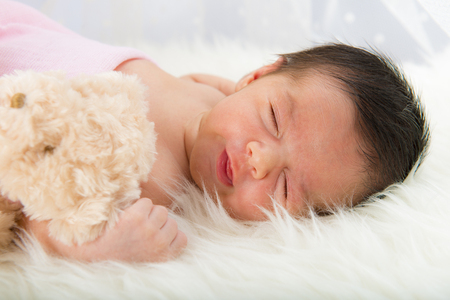 recien nacidos: Feliz niña recién nacida pizca su peluche se relajó en una manta de pelo blanco