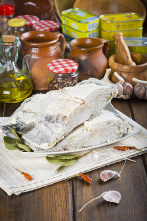salted: Salted cod cut with ingredients and utensils on the table of the kitchen for cooking Stock Photo