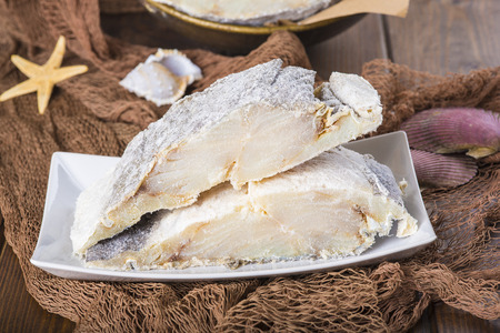 fishing nets: Uncooked salted preserved cod cut in portions on fishing nets Stock Photo