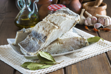 gastronomy: Salted cod cut with ingredients and utensils on the table of the kitchen for cooking Stock Photo