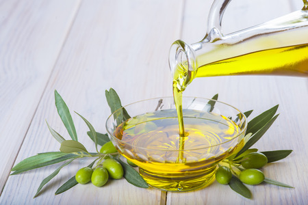 Bottle pouring virgin extra olive oil in a glass bowl