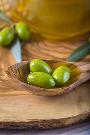 extra virgin olive oil: Green olives and virgin olive oil on a wooden spoon