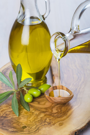 Bottle pouring virgin extra olive oil on a wooden spoon