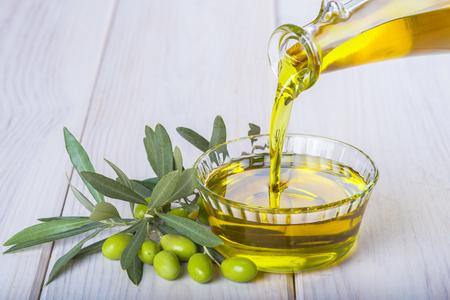 aceite oliva: Botella verter aceite de oliva virgen extra en un recipiente de vidrio