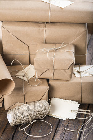 packet: Gifts for Christmas packaged and wrapped on a wooden table Stock Photo