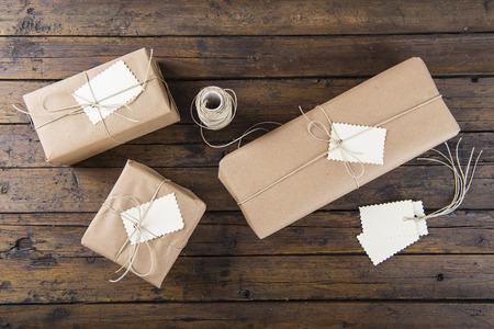 dar un regalo: Regalos para Navidad empaquetados y envueltos en una mesa de madera Foto de archivo