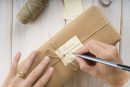text space: A woman is preparing gifts and writing labels for Christmas