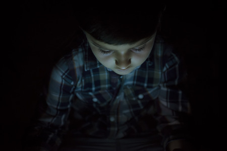 kids playing video games: Child playing with a tablet pc and illuminated by its screen