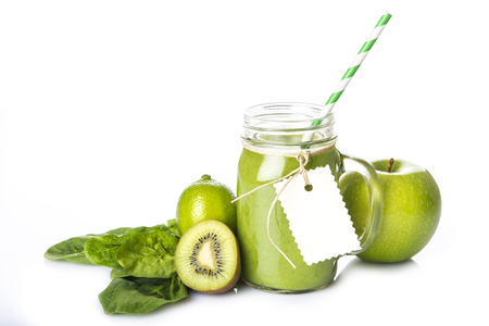 Fresh homemade green smoothie and ingredients isolated on a white background