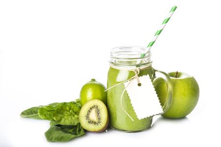 Verse zelfgemaakte groene smoothie en ingrediënten die op een witte achtergrond